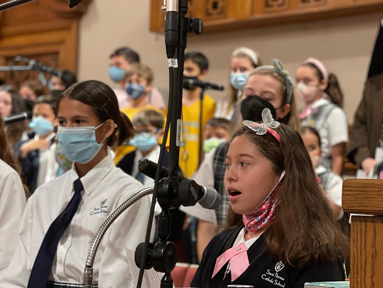 Victoria Biggs and fourth grader Desiree Danger sing in the choir during the school-wide Mass honoring St. Therese at her namesake school in Coral Gables, Oct. 1, 2021.