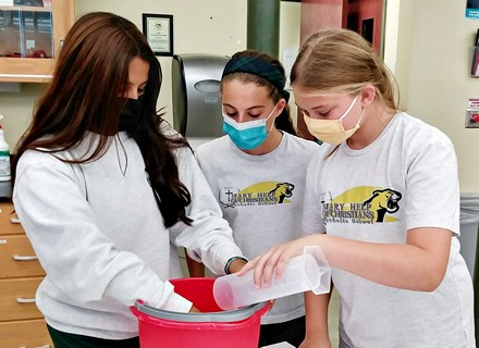 Mary Help of Christians students Sophia Wetmore, Reese Mackenzie and Emi Bernal prepare the growth media for the seeds.
