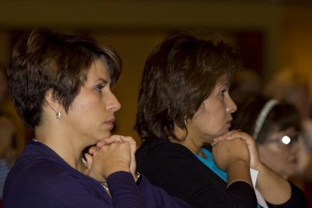 Ivonne Diaz, left, and Miriam Ato of the finance office pray during the Mass.