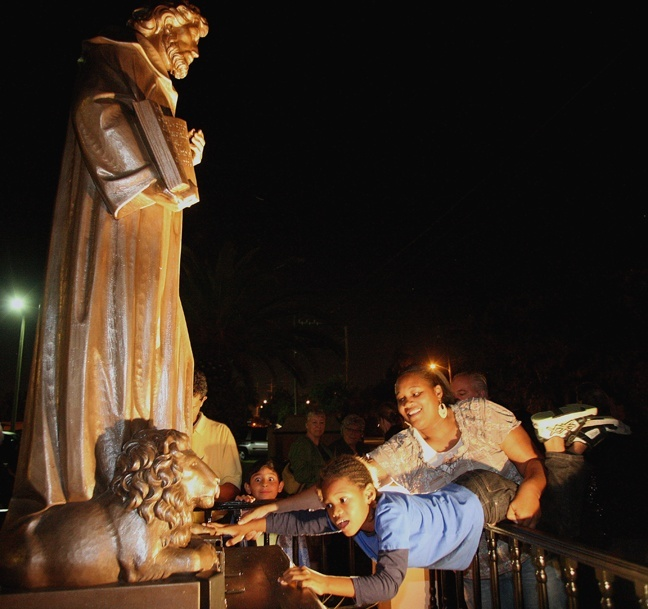 Regine Lamaute helps Khaman Foster, 6, reach out to touch the newly-dedicated bronze statue of St. Jerome, which is inside a fenced-in area in front of the Fort Lauderdale church.