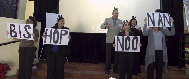 Employees prepare greet Bishop Noonan with a revised version of the Mickey Mouse song.
