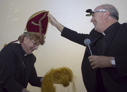 Payback: Bishop Noonan puts on a gag-miter given to him by his classmate in the seminary, Father Federico Capdepon. Over the years, they have kept track of who was going bald faster, so the miter brings with it a full head of red curly hair - and some to spare.