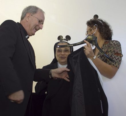 On behalf of all the religious in the archdiocese, Salesian Sister Yamile Saieh and Ileana Roque, his secretary, give Bishop Noonan the gift of a new coat, since the weather gets so much colder in Orlando than in Miami.