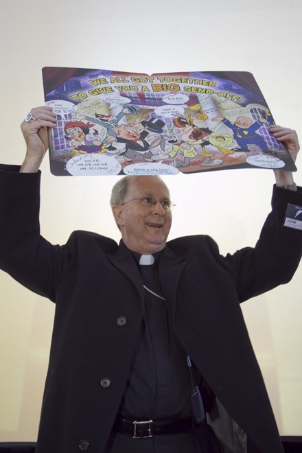 Bishop Noonan holds up one of the two goodbye cards signed by Pastoral Center employees.