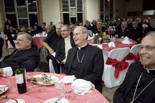 Bishop Noonan sits between Archbishop Wenski, left, and Bishop Estevez during the roast that followed the vespers service at St. John Vianney College Seminary.