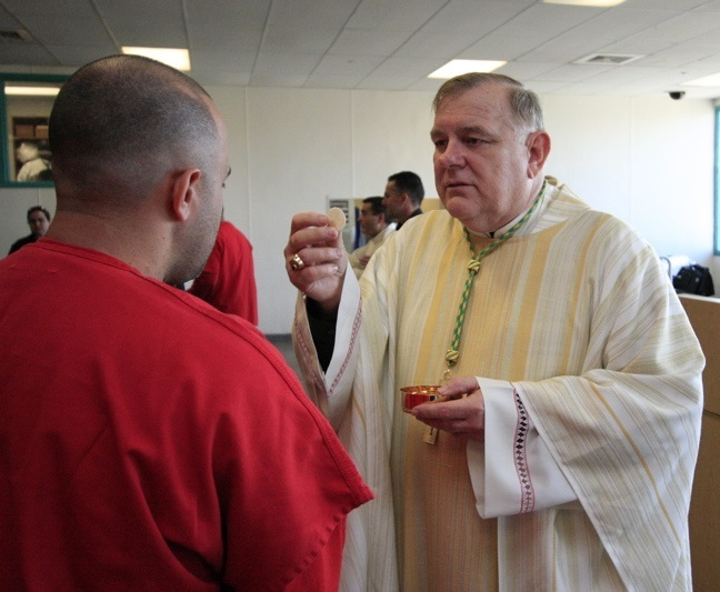 Archbishop Wenski gives communion to a detainee, one of many men being held at Krome from various countries including: Central and South America, the Caribbean, and Africa.