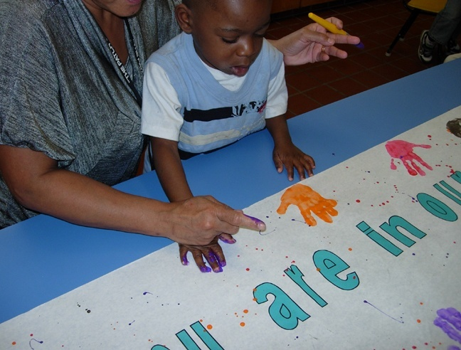 While their parents and others raised funds, children of the Marian Center Inclusive Pre-School in Miami Gardens got busy sending prayers to their counterparts in Haiti. Here, teacher Agnes Powell helps Jamari Desilva put his palm prints on a poster that says,