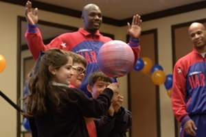 Harlem Globetrotters Big Easy and Flight time teach students how to spin a ball on the tip of a pen.