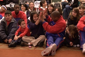 Members of the Harlem Globetrotters sit with students from Blessed Trinity school and enjoy story time.
