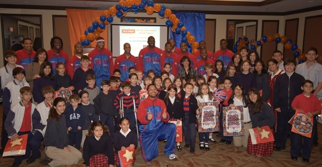 Students and teachers from Blessed Trinity pose with members of the Harlem Globetrotters.