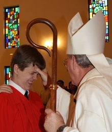 Patrick Goshgarian makes a face as he is anointed by Auxiliary Bishop John Noonan.