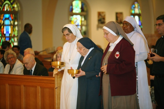 Representatives of religious communities bring up the offertory gifts during the Mass.