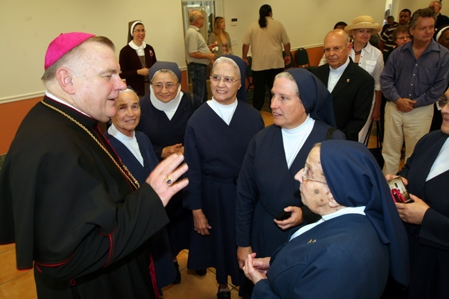 Archbishop Thomas Wenski chats with members of the Daughters of Charity after the Mass.
