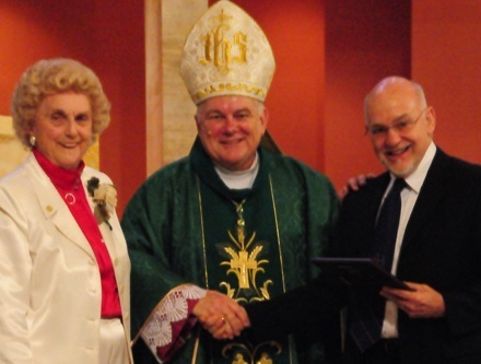 Christian Brother Richard DeMaria, right, receives the Lumen Christi (Light of Christ) award from Marjorie Wessel, president of the Catholic Educators Guild, and Archbishop Thomas Wenski.