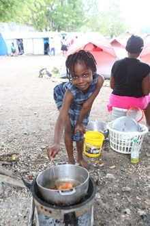 A child cooks a meal at an earthquake refugee tent city in Port-au-Prince.
