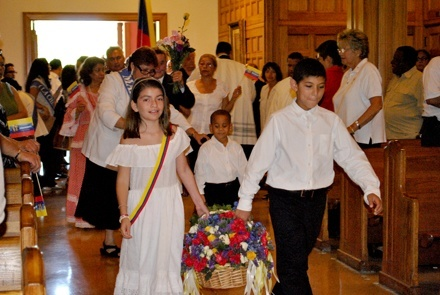 Children, dressed in traditional Colombian clothing, bring flowers up to the image at the start of Mass.