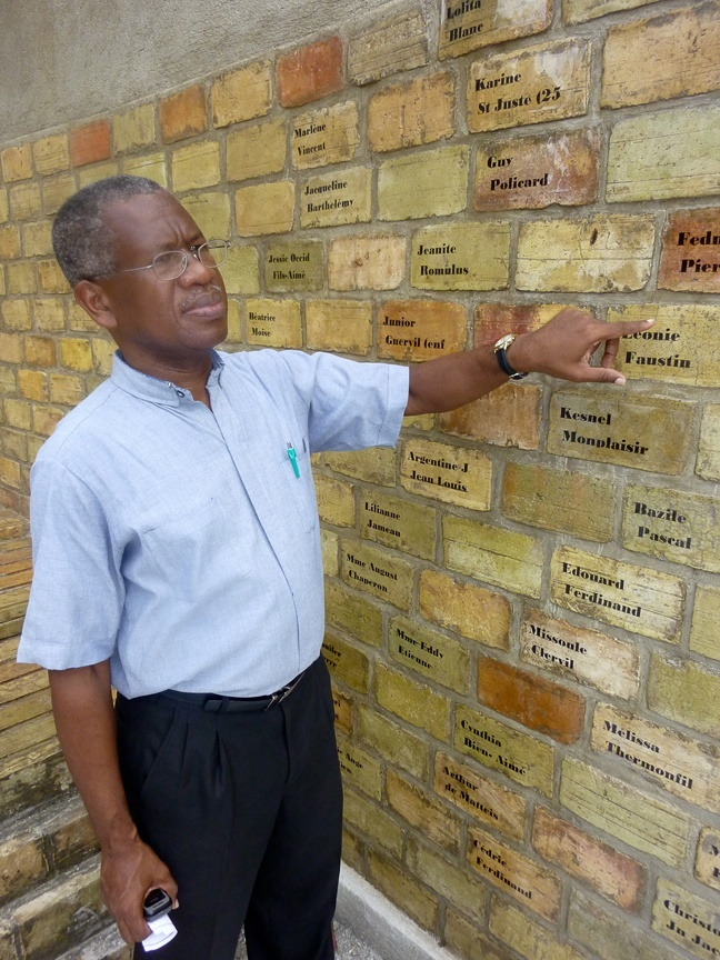 Father Quesnel Alphonse, a Montfort missionary who serves as pastor of the largely destroyed St. Louis King of France Church in Port-au-Prince, points to a brick on the monument that commemorates the victims of the Jan. 12 earthquake, including a fellow Montfort missionary who worked with him at the parish.