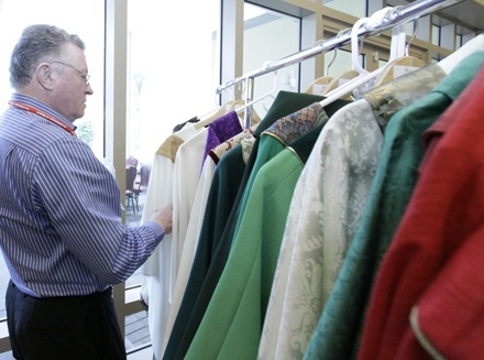 Msgr. Jude O'Doherty, pastor of Epiphany Parish in South Miami, checks out the cassocks exhibited by vendors at the convocation.
