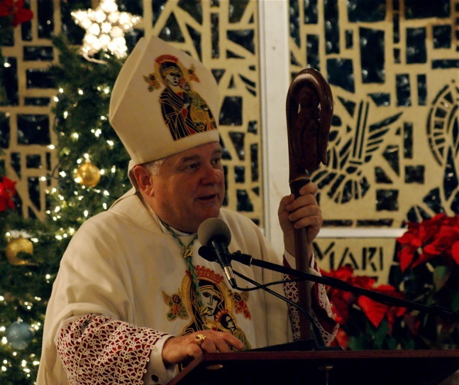 Archbishop Thomas Wenski preaches the homily during the midnight Mass at Notre Dame d' Haiti Mission celebrating the New Year.