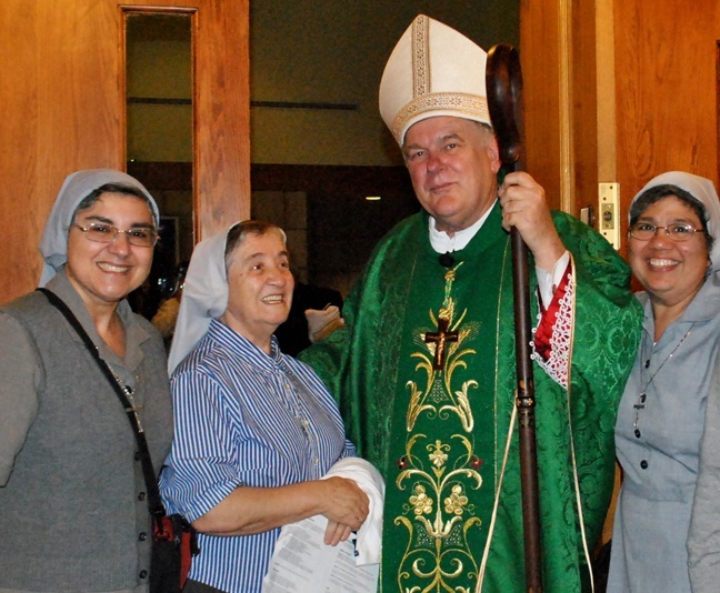 From left, Sister Ondina Cortes, Sister Carmen Alvarez and Sister Claudia Ortiz, three of the five Claretians working in the Miami archdiocese, pose with Archbishop Thomas Wenski after Mass.