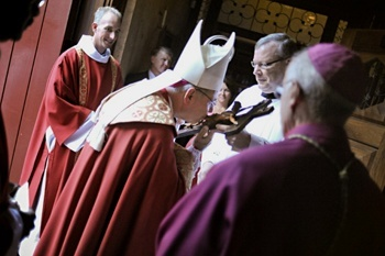 Bishop Estevez kisses the cross inside the Cathedral- Basilica of St. Augustine.