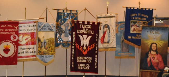 A row of banners represents each of the different Hispanic charismatic groups within the Archdiocese of Miami.