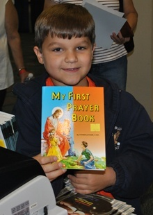 Brayden Franks shows off his first prayer book, which he bought at the conference, where vendors of Catholic material sold books, rosaries and other religious goods.
