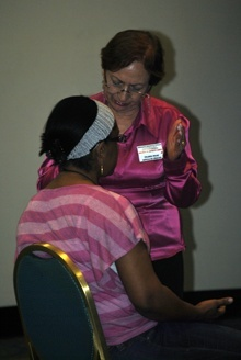 Prayer team member Yolanda Rojas prays for a participant at the conference.