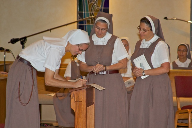 Sister Rachel Marie of the Eucharistic Lamb signs the formula for profession of vows for the Servants of the Pierced Hearts of Jesus and Mary in front of her religious superiors, Mother Adela Galindo, foundress of the order, center, and Sister Ana Margarita Lanzas.