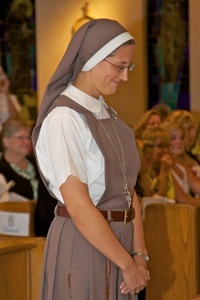 Sister Grace Marie of the Triumph of Crucified Love stands after receiving her full habit and veil.