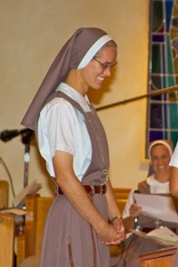 Sister Rachel Marie of the Eucharistic Lamb stands after receiving her full habit and veil.