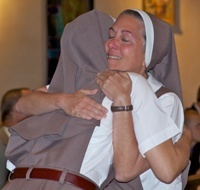 After vesting with the full habit, Sister Grace Marie of the Triumph of Crucified Love receives a hug from Mother Adela Galindo, foundress of the Servants of the Pierced Hearts of Jesus and Mary.