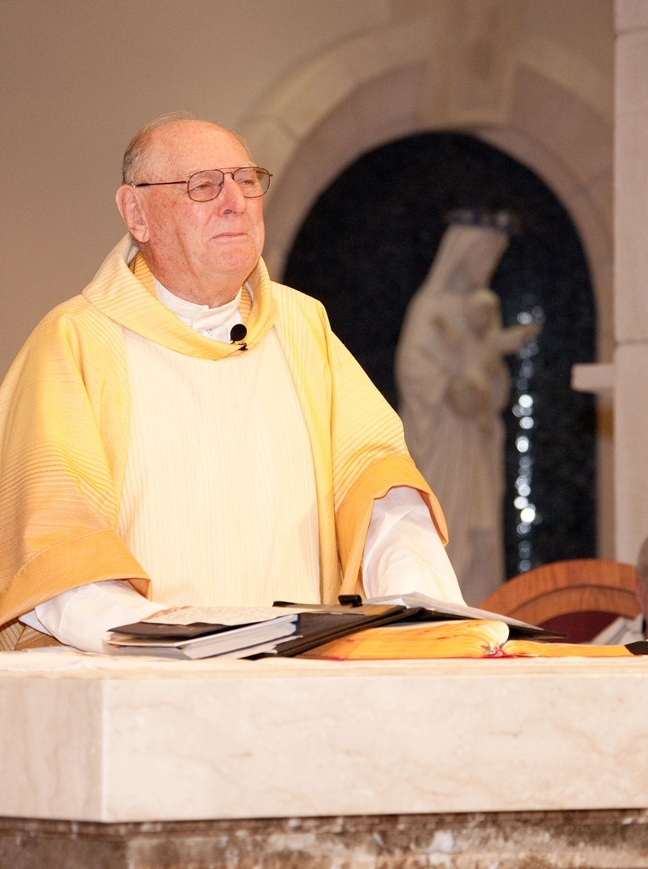 Msgr. Noel Fogarty prays at altar during his last Mass as pastor of St. Gregory the Great Parish in Plantation.