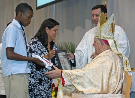 Pace senior Moise Jerome and Monica Lauzurique of the lay missionary group Amor en Accion, present the archbishop with symbols of the high school's commitment to service during the offertory.