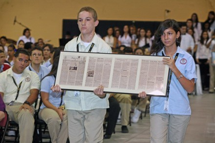 Sophomores Alejandro Hernandez and Elexa Suarez carry a framed copy of the Nov. 1, 1963 edition of the Pace High School newspaper, Kerygma, during the offertory procession.