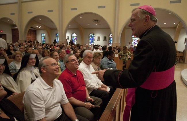 Archbishop Thomas Wenski talks with Synod focus team members before the start of the Mass.