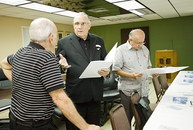 Deacon Dennis Jordan, center, of Blessed Trinity Parish speaks with Deacon Carl Carieri of St. Maximilian Kolbe as Deacon Roberto Pineda of St. Joseph Parish looks over the Synod focus team documents.
