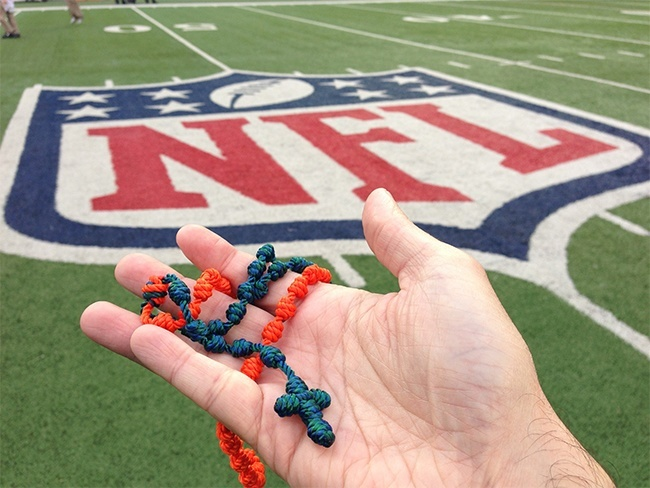 Father Manny Alvarez holds an aqua and orange rosary made by a St. Gregory parishioner, a rosary he prays while standing on the sidelines at Dolphins games.