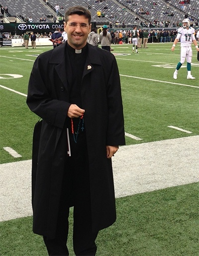 Father Manny Alvarez stands on the sidelines before the start of the Dolphins game against the New York Jets Oct. 28, holding an aqua and orange rosary made by a St. Gregory parishioner.