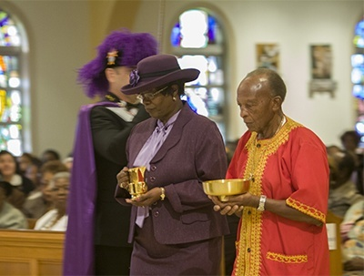 Katrenia Reeves-Jackman, director of the Office of Black Catholic Ministry, and Charles Thompson, president of the Black Catholic Implementation Team, take up the offertory.