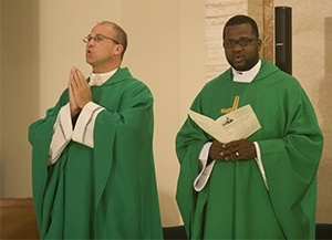 Father Christopher Marino, rector of St. Mary Cathedral, left, takes part in the Mass along with Father Chanel Jeanty, archdiocesan chancellor and pastor of St. Philip Neri Church in Miami Gardens.