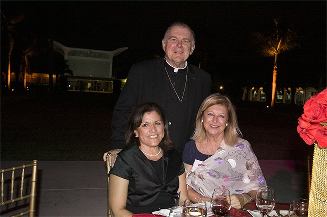 Archbishop Thomas Wenski poses with Reyna Jovel, left, and Danoushka Capponi of St. Joseph Parish in Miami Beach. Behind them is St. Raphael Chapel, the centerpiece building on the campus of St. John Vianney College Seminary.
