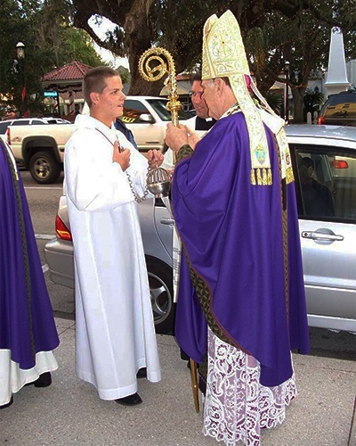 As they wait for the start of the Mass outside the Cathedral Basilica of St. Augustine, Archbishop Thomas Wenski explains the use of incense to altar server Fillipo Schiavo.