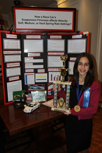 "First place winner Daniela Rodriguez, a sixth grader at Blessed Trinity School, poses with her first place trophy. She will go on to represent Miami-Dade County and Blessed Trinity in the 57th annual Florida State Science Fair to be held in Lakeland this April. Daniela's winning project was ""How a Race Car's Suspension Firmness Affects Velocity: Soft, Medium, or Hard Spring Rate Settings."
