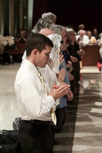 Participants at the Mass kneel at the front of the altar in preparation for receiving Communion.