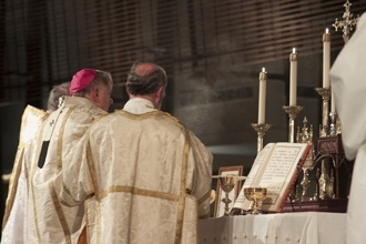Accompanied by priest-deacons, Archbishop Thomas Wenski incenses the altar before the consecration.