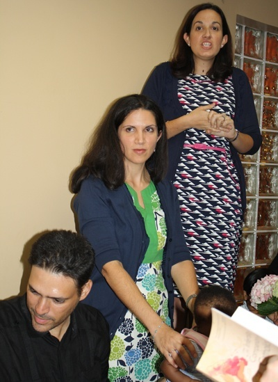 Co-authors Angelique Ruhi-Lopez, rear, and Carmen Santamaria speak at the book signing that followed the Mass. Santamaria's husband, Alejandro, is below in front.