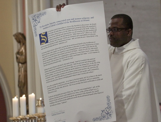 Father Chanel Jeanty, archdiocesan chancellor for canonical affairs, shows the congregation and priests the scroll proclaiming the start of an archdiocesan synod, the second in the history of the Miami archdiocese.