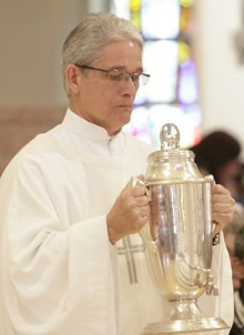 A deacon brings up the the oil of chrism which is used in confirmations and ordinations.