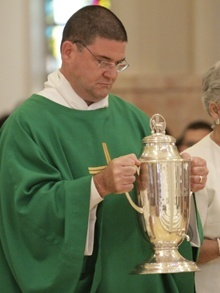 A deacon brings up the the oil of catechumens which is used in baptisms.
